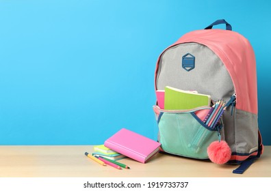 Stylish backpack and different school stationery on wooden table against light blue background, space for text. Back to school