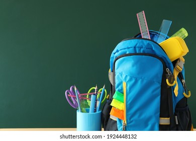 Stylish backpack and different school stationery near green chalkboard, space for text. Back to school