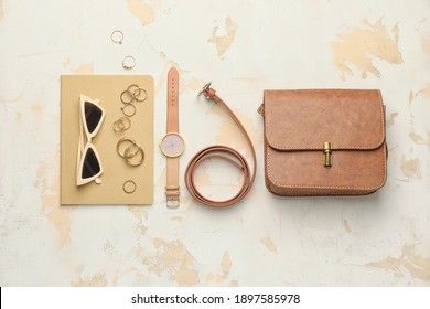 Stylish bag with female accessories on white background