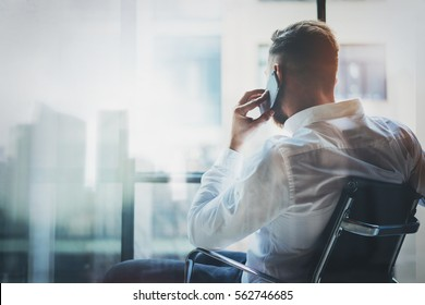 Stylish banker making mobile call at modern loft after work day.Man sitting in chair and looking out the panoramic window.Skyscraper office building blurred on background.Horizontal