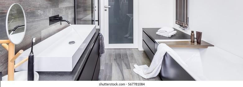 Stylish bathroom with bathtub, countertop basin and wall heater, panorama