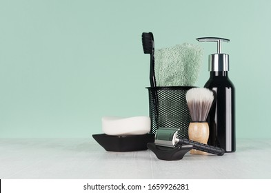 Stylish bathroom interior with black shaving accessories on green  wall, white table - razor, toothbrush, towel, soap, shave brush, dispenser.
