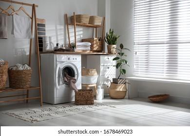 Stylish bathroom interior with modern washing machine