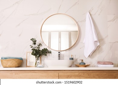 Stylish bathroom interior with vessel sink and round mirror