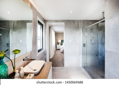 Stylish bathroom with a wood finish sink and a glass division shower, attached to a bathroom.