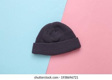 Stylish beanie hat on blue pink pastel background
