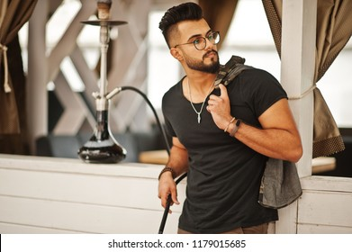 Stylish beard arabian man in glasses and black t-shirt smoking hookah outdoor. Arab model having rest.
