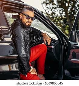 Stylish beard handsome man in a car - outdoor fashion portrait