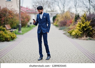 Stylish beard indian business man with bindi on forehead, wear on blue suit posed outdoor looking at mobile phone.