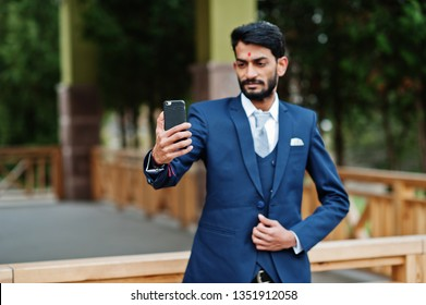 Stylish beard indian business man with bindi on forehead, wear on blue suit posed outdoor and making selfie at mobile phone.