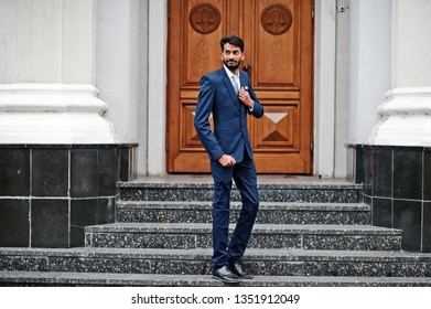 Stylish beard indian man with bindi on forehead, wear on blue suit posed outdoor against door of building.
