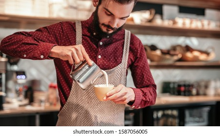 Stylish bearded bartender pouring milk into coffee while preparing cappuccino during work in cozy cafeteria
