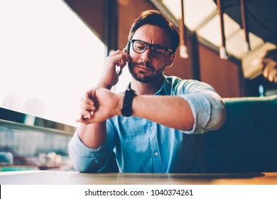 Stylish bearded businessman 30 years old looking at smartwatch while solving financial promlems during mobile conversation.Male entrepreneur talking on smartphone about meeting with partner in cafe