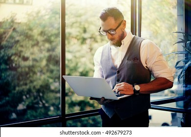 Stylish Bearded Businessman Wearing Glasses White Shirt Waistcoat Working Modern Laptop Holding Hands Near Panoramic Window.Man Work Office Startup Project.Sunlight Effect.Blurred Background