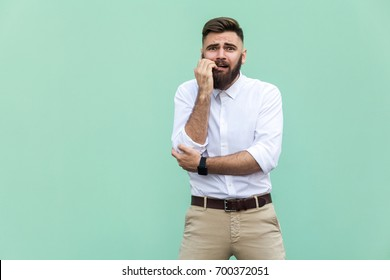 Stylish bearded businessman with worried. Hipster guy having shocked face, looking at camera. Indoor, studio shot, light green background