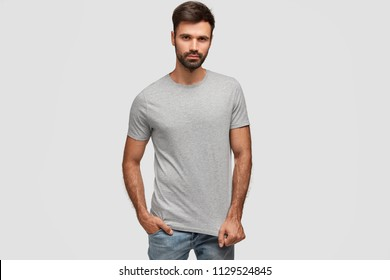 Stylish bearded handsome male with thick dark stubble, dressed in casual t shirt, keeps hand in pocket of jeans, looks self assured, fond of fashion, isolated over white background. Masculinity
