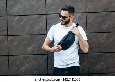 Stylish bearded hipster in the at the city in a white T-shirt with waist bag