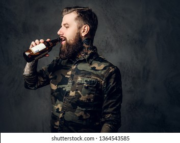 Stylish bearded hipster guy in military shirt enjoys the taste of craft beer. Studio photo against a dark wall