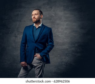 A stylish bearded hipster male dressed in a suit and sunglasses over dark grey background.