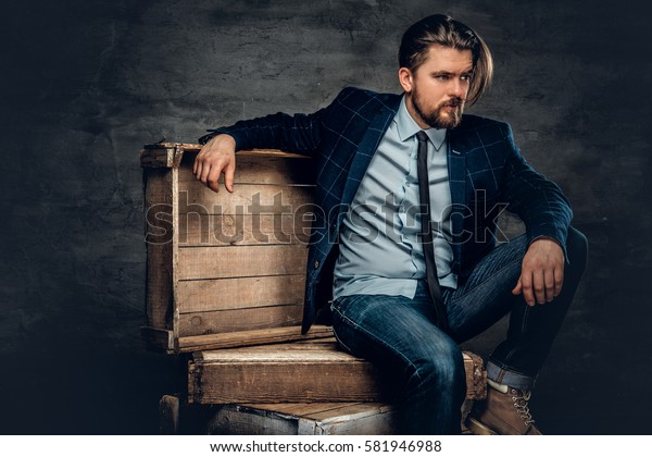 The stylish bearded hipster male sits on a wooden box in a studio over dark grey background.