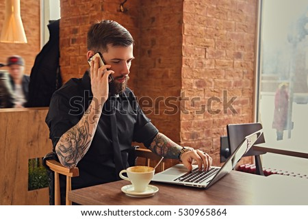 Stylish bearded hipster male talking by smartphone and using a laptop in a coffee shop.