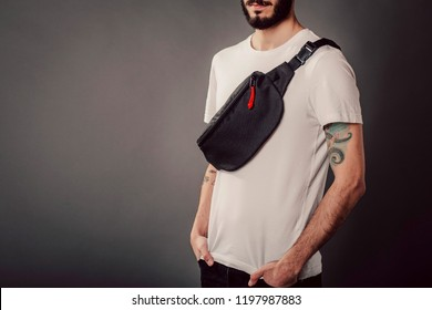 Stylish bearded hipster in the studio in a white T-shirt with waist bag