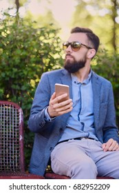 Stylish bearded male in a blue jacket using smartphone in a park.