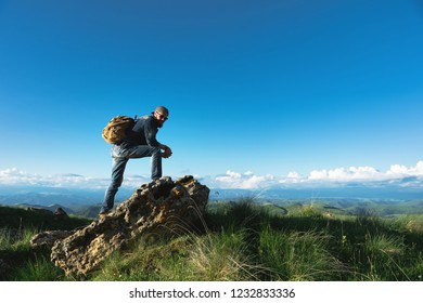 Stylish bearded male traveler in sunglasses and a cap with a backpack in a denim suit and yellow shoes stands on a large stone against the background of an evening horizon. Travel and look to the