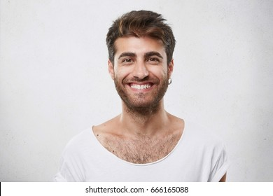 Stylish bearded man with appealing dark eyes smiling into camera having pleased expression being glad to meet his girlfriend. Hipster guy with beard grinning having cheerful look. Positive emotions