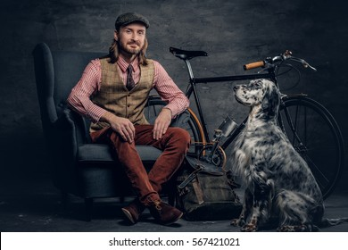 A stylish bearded man in a cap sits on a chair with an Ireland setter dog and a bicycle on a background.