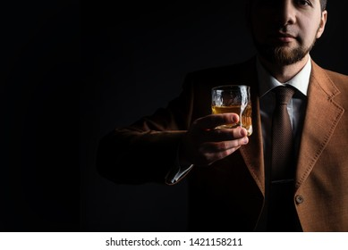 Stylish bearded man in elegant jacket holds whiskey glass and to
