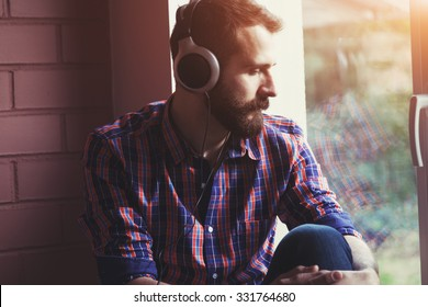 stylish bearded man  in headphones listening to music near window with reflection