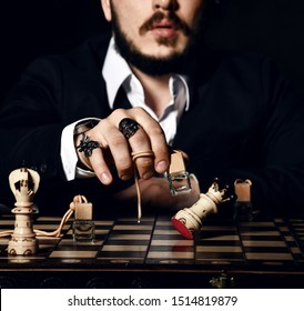 Stylish bearded man in official black jacket, white shirt and with brutal signet rings playing chess with bottle of perfume, making a move, attack white queen on dark background