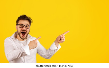 Stylish bearded man in shirt and glasses pointing away with amazement while showing new offer on yellow background