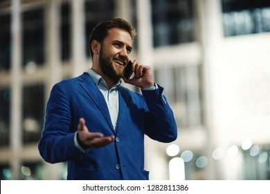 Stylish bearded man in suit having call on smartphone smiling away standing on street in lights