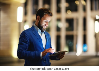 Stylish bearded man in suit using tablet on street in glowing lights of illuminated building in night time