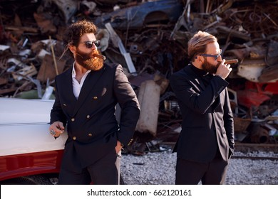 Stylish bearded mens in black suits and sunglasses smokes cigars on the iron dump background and looks at the one sided confidence .Gentlemen's club.Horizontal view.
