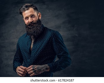 A stylish bearded tattooed male dressed in dark blue jacket over grey background.