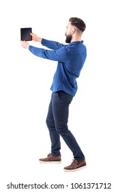 Stylish bearded young man taking selfie photo with tablet or large mobile phone. Side view. Full body isolated on white background.