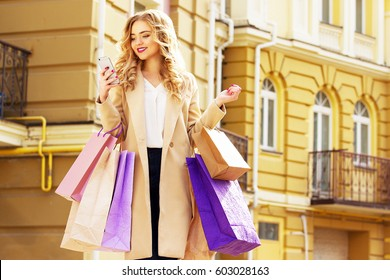Stylish, beautiful blonde hair smiling girl with purchases and using her phone. Happy shopping.