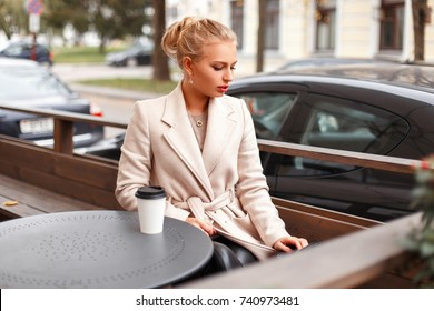 Stylish beautiful business woman in a classic trendy coat resting in a cafe on the street