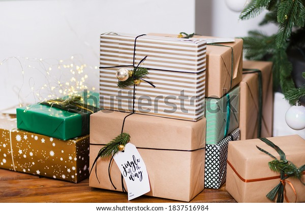 Stylish and beautiful Christmas gifts in craft paper, green paper and golden lie under the tree