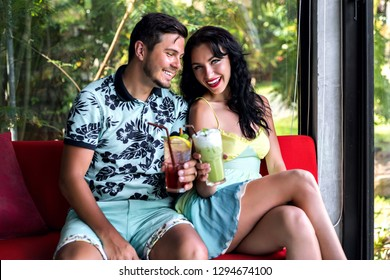 Stylish beautiful couple enjoy time and vacation together, posing at tropical luxury restaurant, trendy summer outfits, drinking tasty beverages, relationships goals.