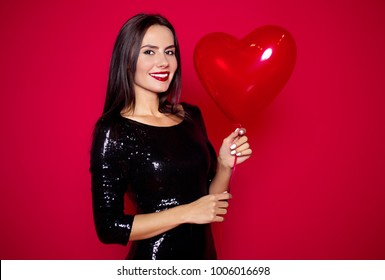 Stylish beautiful elegant smiling woman in a little black dress with a red balloon. Women's Day. Valentine's Day.