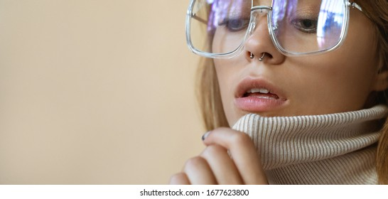 Stylish beautiful fashion girl with nose piercing wear trendy sunglasses. Retro vintage sexy attractive young model woman blond hair in eyewear on beige studio background. Close up banner, copy space.