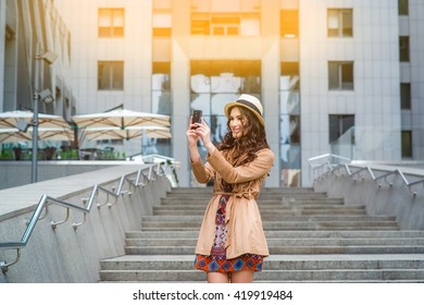 Stylish beautiful girl dressed in boho style with a smartphone on the background of the business center. Smiling woman doing selfie phone.