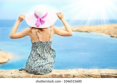 Stylish beautiful girl in hat on the seashore background