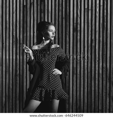 44baef83c12 Stylish beautiful girl wearing polka-dot black white dress posing outdoors  against wooden wall at sunset. Young pretty woman smoking cigarette - Image