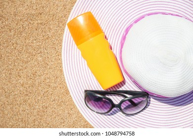 Stylish beautiful hat with cream on the seashore background