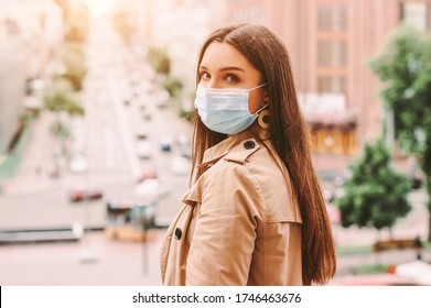 Stylish beautiful hipster girl in medical face mask, trench coat on city street. Young happy woman in protective face mask outdoors. Quarantine lifestyle, urban fashion, COVID-19 coronavirus, travel